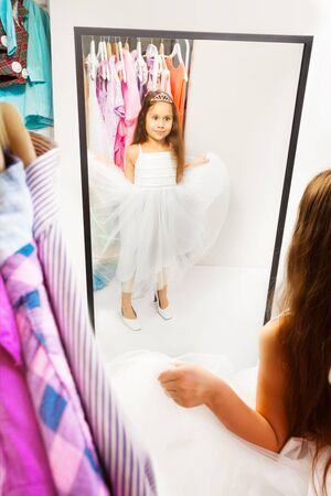 changing clothes: Beautiful little girl try dress before the mirror Stock Photo