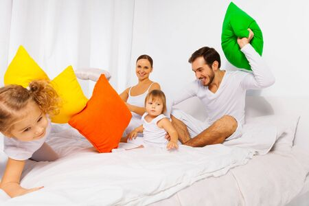family fight: Happy father, mother and kids play with pillows Stock Photo