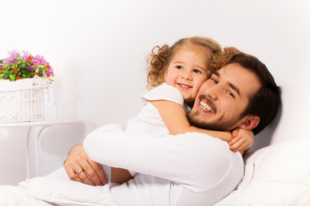 Smiling father and daughter hug on the white bed