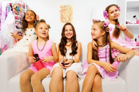 five people: Happy girls with hair-curlers sit on white sofa
