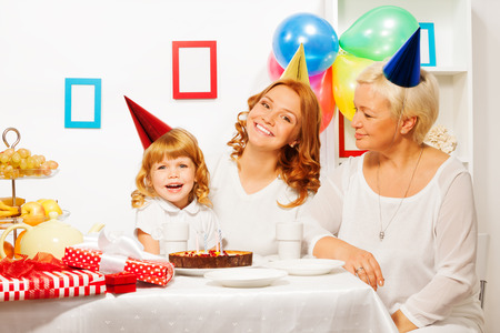 tea candles: Little girl with mother and granny on birthday Stock Photo
