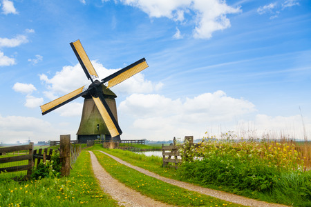 Rural road and windmill in Netherlands Imagens