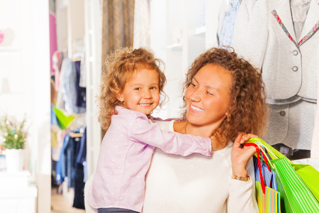 Small cute girl with her beautiful mother shopping photo