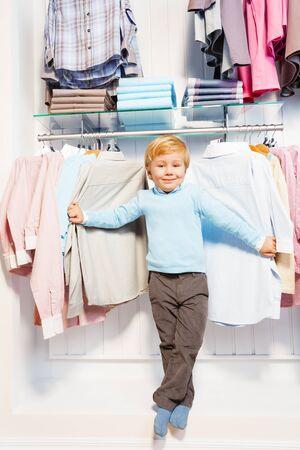 shopaholics: Boy standing among clothes on hangers and shelf