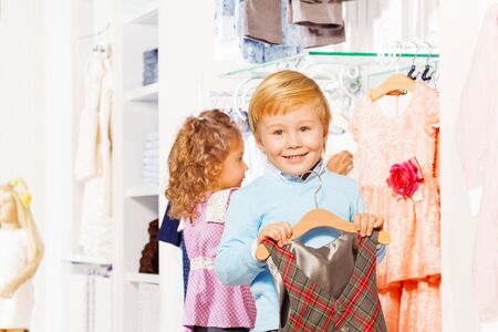 choosing clothes: Boy with hanger and girl behind choosing clothes