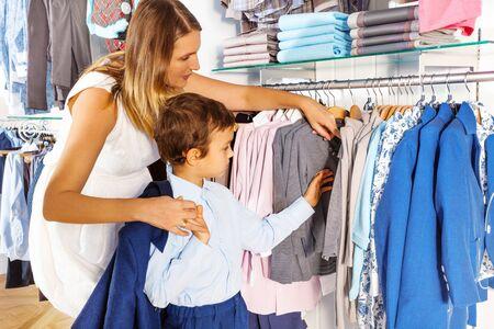 ropa colgada: Madre con el niño busca en la ropa mientras que las compras
