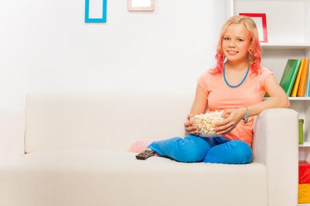 bowl of popcorn: Happy girl holding bowl with popcorn on white sofa Stock Photo