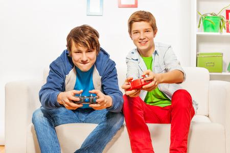 Gelukkige vrienden houden joysticks en play game console Stockfoto