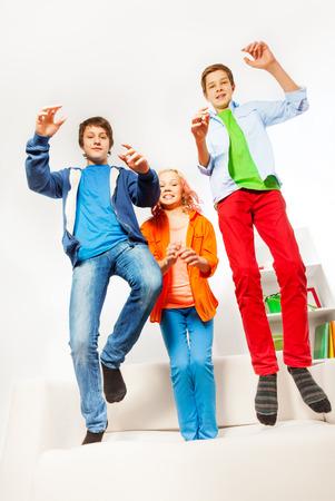 happy teenagers: Three happy teenagers jumping on white sofa