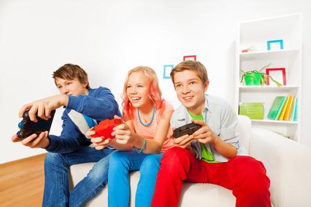 niños jugando videojuegos: Chica y chicos con consola joysticks juego de juego
