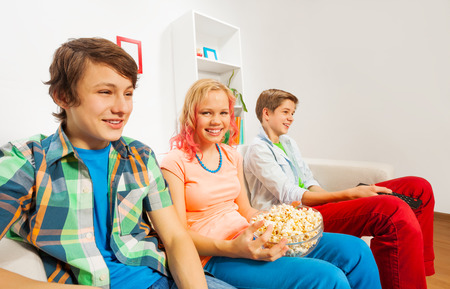 happy teenagers: Happy teenagers hold popcorn and sit on sofa