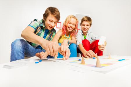 jeu de carte: Fille et deux garçons jouant jeu de table à la maison
