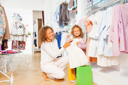 Small smiling girl with beautiful mother shopping photo