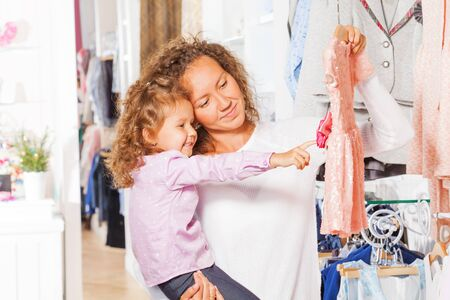 Small cute girl with her mother choosing dress photo