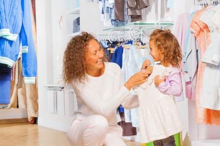 Happy mother trying dress on her daughter photo