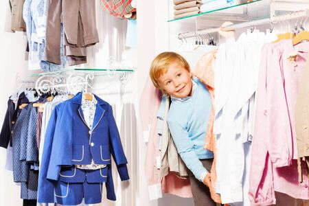 hide and seek: Blond small boy playa hide-and-seek in clothes