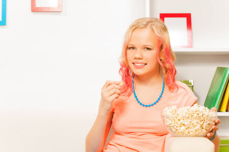 bowl of popcorn: Smiling girl holding bowl with popcorn at home