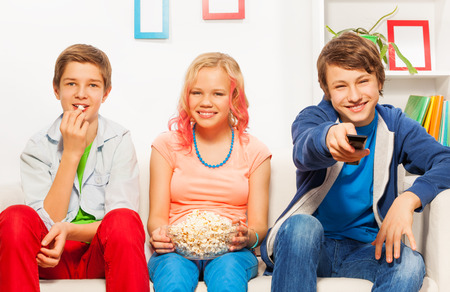 room mate: Three smiling friends eat popcorn together on sofa Stock Photo