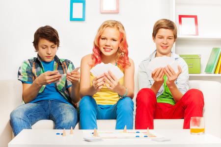monopolio: Tres adolescentes que juegan al juego de mesa en el sofá blanco