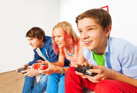jugando videojuegos: Tres amigos con consola joysticks juego de juego Foto de archivo