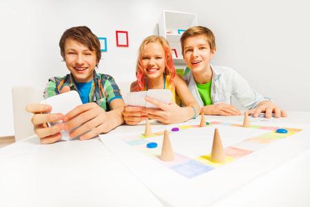 monopolio: Adolescentes felices que juegan juegos de mesa tarjetas de cartera