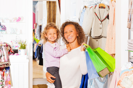 Girl with happy mother holding bags while shopping photo