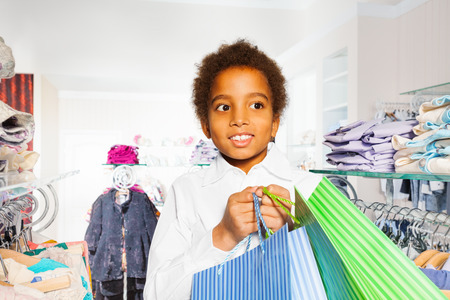 african fashion: African boy between hangers holds shopping bags