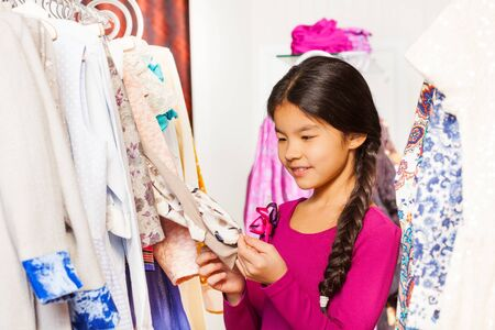 choosing clothes: Cute Asian girl with braid choosing clothes