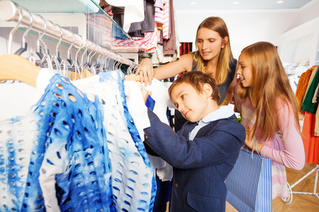Children and their mother search clothes in store photo