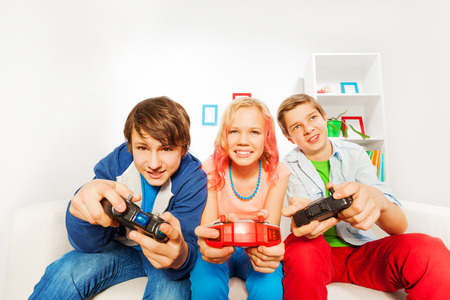 Excited teens hold joysticks and play game console