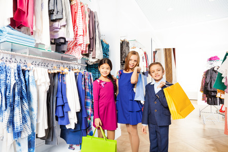 Two smiling girls and boy with shopping bags photo