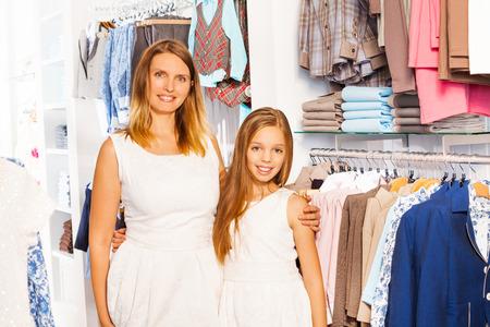 ni�os de compras: Linda chica con su madre en el equipo blanco en la tienda