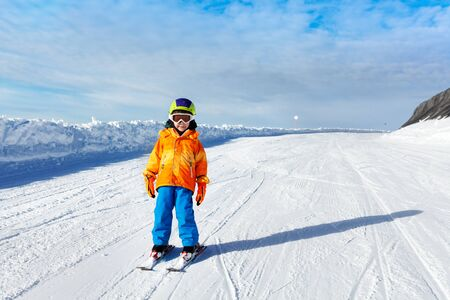 ski mask: Small boy wearing ski mask stands on ski-track