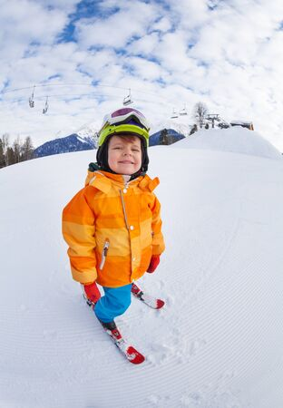 ski mask: Cheerful boy wearing ski mask and helmet skiing Stock Photo