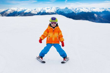 ski mask: Boy wearing ski mask and helmet skiing on slope Stock Photo