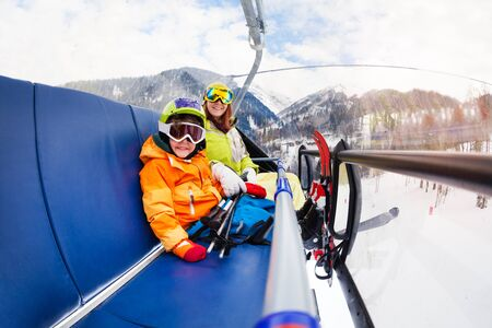 ski goggles: Little boy and mother on ski lift chair Stock Photo