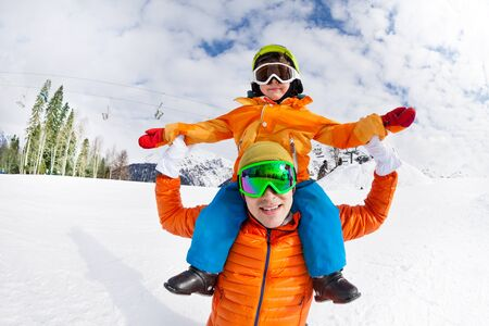 lifestyle outdoors: Father and son sitting on shoulders, snow day