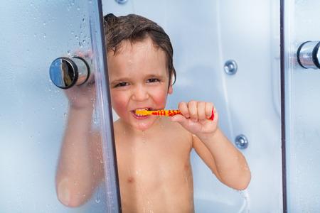 cabine de douche: Mignon petit gar�on utilisation brosse � dents dans la cabine de douche Banque d'images