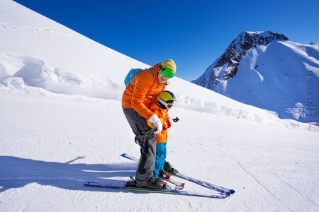 skiing: Instructor give ski lesson to little boy