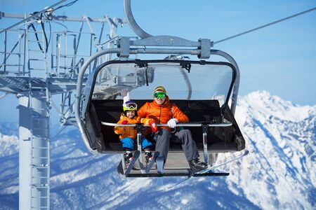 Father and boy sit in ski lift over mountains photo