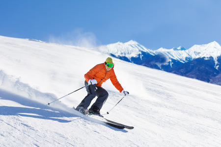 ski mask: Young man in ski mask sliding fast while skiing Stock Photo