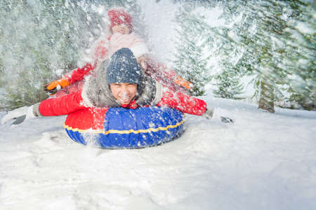 during the day: Happy friends on snow tube in winter during day Stock Photo