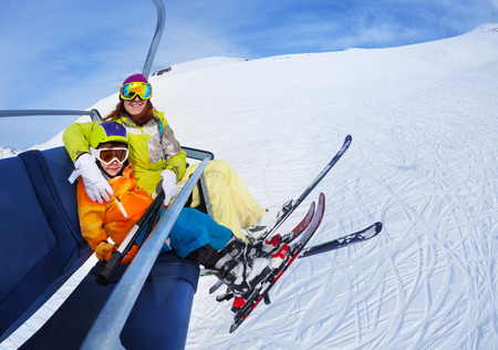 ropeway: Little skier boy with mother lift on mountain Stock Photo