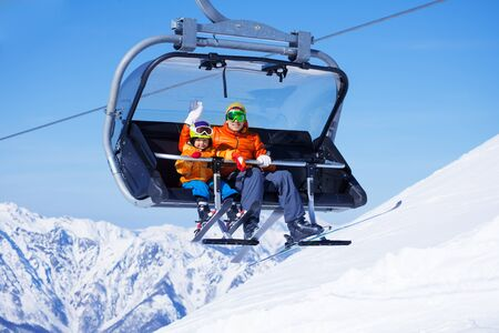 Boy and dad sit in chair lifting on the mountain photo