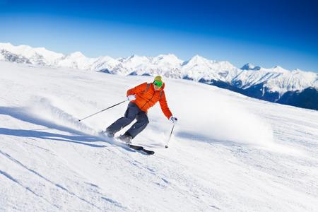 Skiër in masker dia's snel tijdens het skiën van de helling