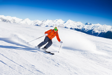 hill: Skier in mask slides fast while skiing from slope Stock Photo