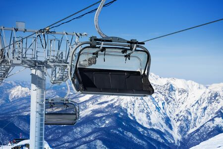 chairlift: Close view of chairlift and mountains on resort