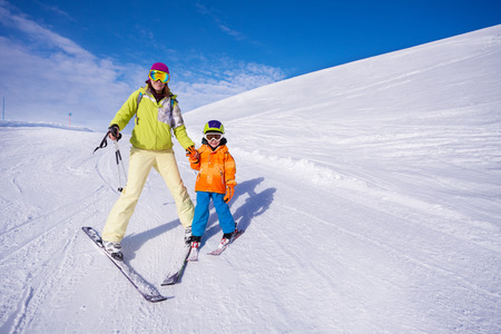 ski resort: Mother and little boy learning to ski holding hand