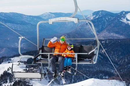 Man skier with child lift on ropeway chair photo