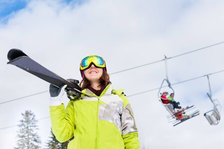 ski lift: Happy woman in mask with ski lift behind her